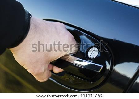 Hand is opening the car door - stock photo