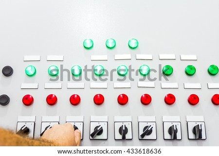 Hand is operating a heavy duty switch on electrical cabinet providing electrical energy to residential place. - stock photo