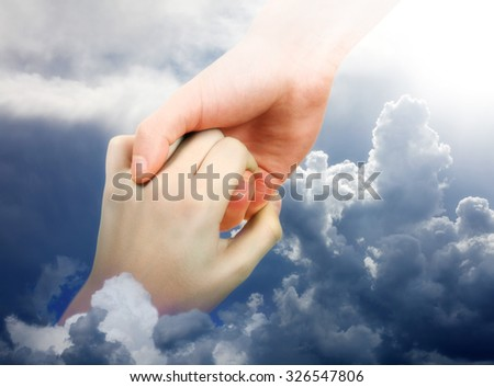 Hand is reaching out for the Help from another Hand in the Clouds - stock photo