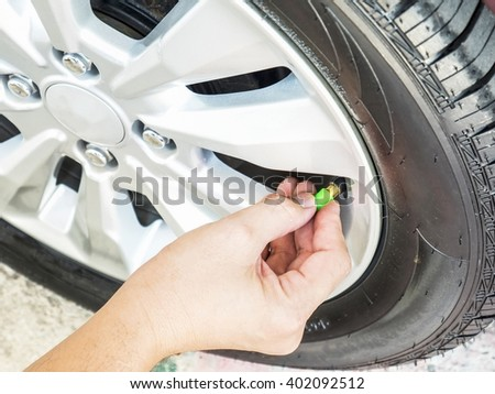 Hand is removing a green tire valve caps for nitrogen tire inflation service