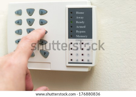 Hand is setting home security alarm system