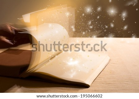 Hand leafing through a book with blank pages magic light. Education - stock photo