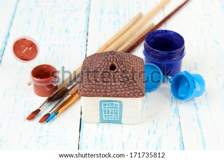 Hand made ceramic house and color paints on wooden table - stock photo
