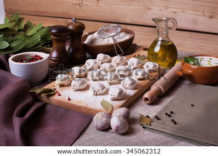 hand-made dumplings on the board with flour and ingredients rural village board bay leaf still-life plank wood flour ingredients appetizing nourishing hand modeling - stock photo