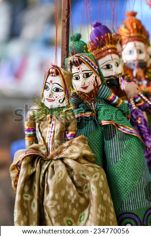 hand made puppets attached to string in Rajasthan India dolls. Women face with traditional Indian makeup wearing saree Diwali dasara