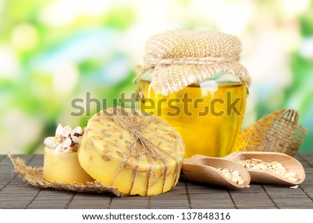 Hand made soap and ingredients for soap making on bamboo mat, on green background - stock photo