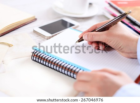 hand makes a note in notebook - stock photo
