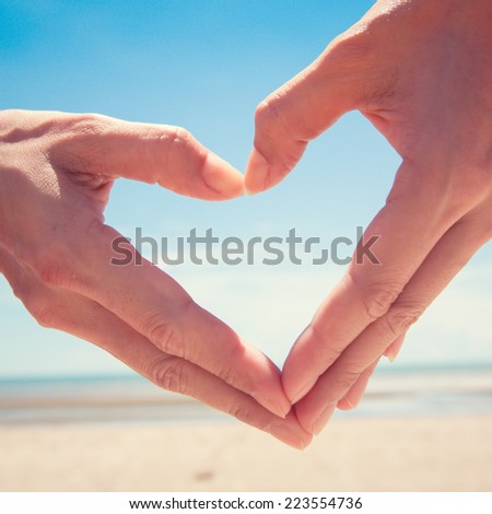 Hand making heart shape with beautiful beach and sky background. - stock photo