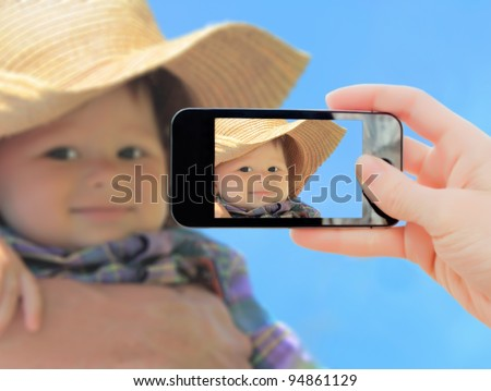 Hand making shot of little boy in cowboy hat - stock photo
