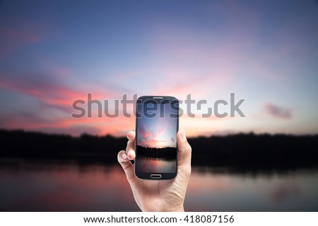 Hand male Asian holding Smartphone taking picture of Twilight ,with Sea the dawn sun . Overcast. - stock photo
