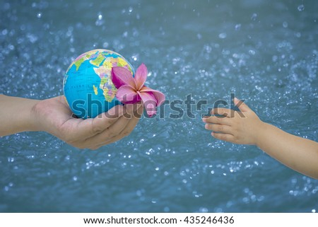 hand male gesture holding the worldon on blurred cyan turquoise blue wavy water background, human hands with healthy world concept, love and safe conception. - stock photo