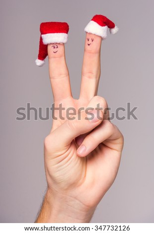 Hand man dressed in Christmas hats for little fingers, isolated on a white background - stock photo