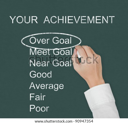 hand marking over goal achievement on chalkboard