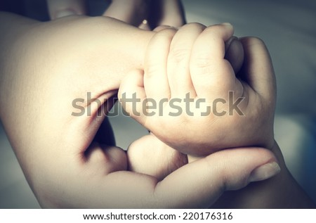 Hand mother holds the hand of a baby, close-up - stock photo
