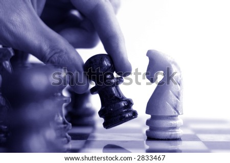 Hand moving a chess piece across the board, closeup - stock photo