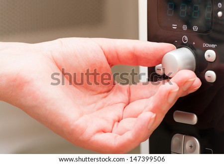 Hand moving the timer knob on the microwave oven - stock photo