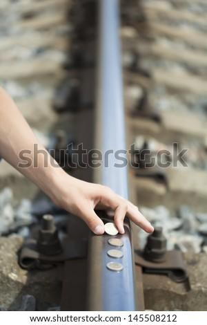 Hand near euro coins on the rails - stock photo