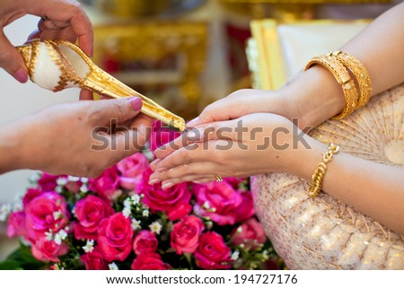 hand of a bride receiving holy water from elders in thai culture wedding ceremony  - stock photo