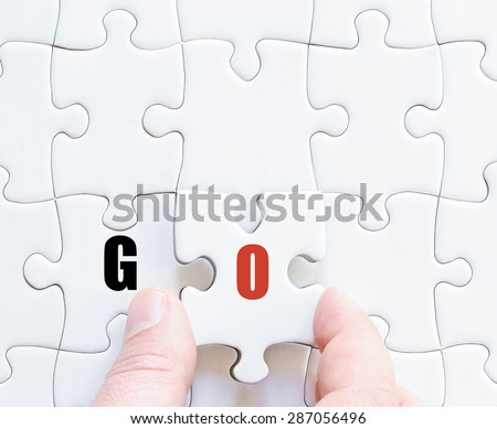 Hand of a business man completing the puzzle with the last missing piece.Concept image of puzzle board with motivational  word GO
