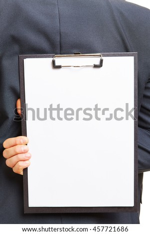 Hand of a business man holding clipboard with white paper behind his back - stock photo