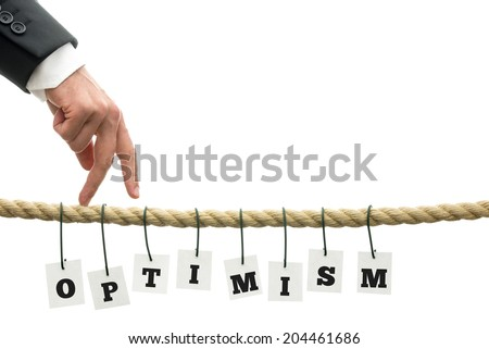 Hand of a business man making the walking gesture on a rope with hanging tags with black majuscule letters forming the word optimism, with copy space on white. - stock photo