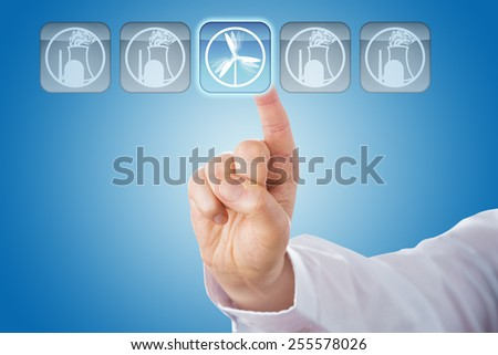 Hand of a business man selecting a wind energy icon in a row of nuclear power symbols. His right index finger is touching the highlighted push button from behind. Blue gradient background. Close up. - stock photo