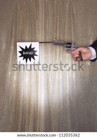 Hand of a businessman holding pistol with bang flag - stock photo