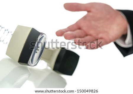 Hand of a businessman showing towards telephone receiver on a white desk with reflection.