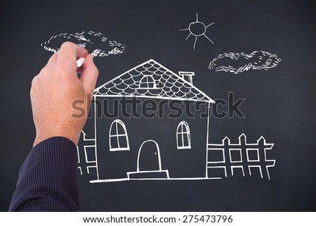 Hand of a businessman writing with a chalk against black background