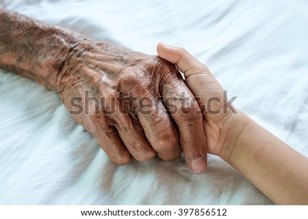 hand of a child and old man on white table cloth on a white bed in a hospital.