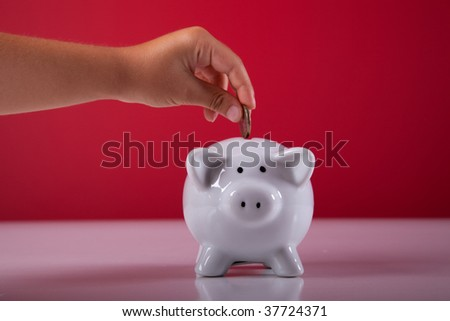 hand of a child saving some money on his piggy bank - stock photo