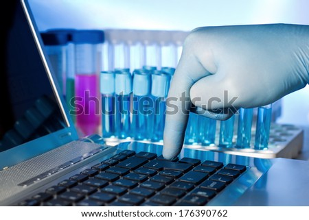 hand of a doctor in lab pressing the Enter key on computer - stock photo