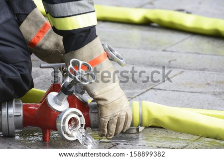 Hand of a fireman connecting a firehose to an outlet. - stock photo