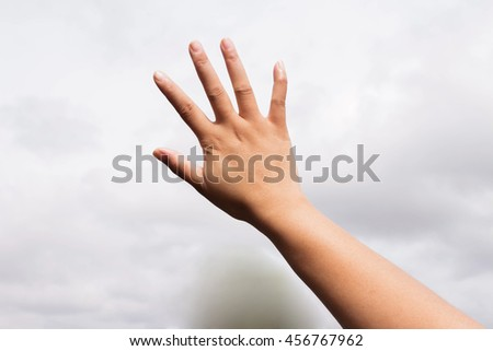 Hand of a girl on sky  background - stock photo