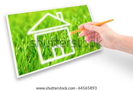 Hand of a girl with a pencil drawing a house of dream against the green grass. - stock photo