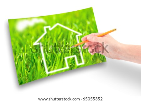 Hand of a girl with a pencil draws a house against on the green grass. - stock photo