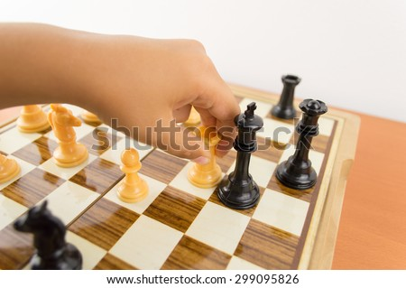 hand of a kid playing chess moving the rook to kill the king - making the checkmate - stock photo