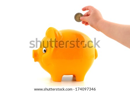 Hand of a little child in front of a yellow piggy bank - stock photo