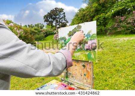 Hand of a male painter finishing his glorious  picture on a sketchbook standing in a garden in front of beautiful blue sky - stock photo