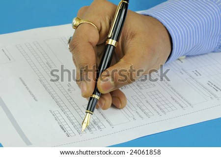 hand of a man filling an application form wearing formal shirt and using expensive fountain pen - stock photo