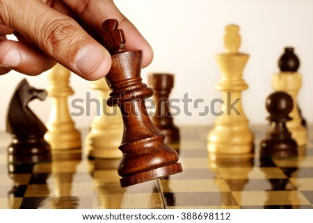 Hand of a man going for checkmate-Game of chess  - stock photo