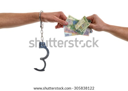 Hand of a man in handcuffs giving bribe - stock photo