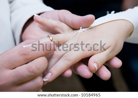 hand of a man put on a wedding ring on the finger of the bride