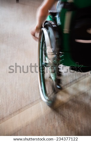 hand of a man sitting in a wheelchair. wheelchair in motion