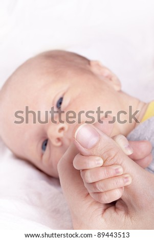 hand of a newborn baby girl holding the thumb of her mother - stock photo