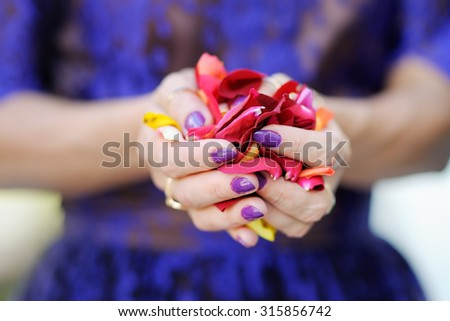 Hand of a woman full of rose petals ready to throw, focus on petals  - stock photo