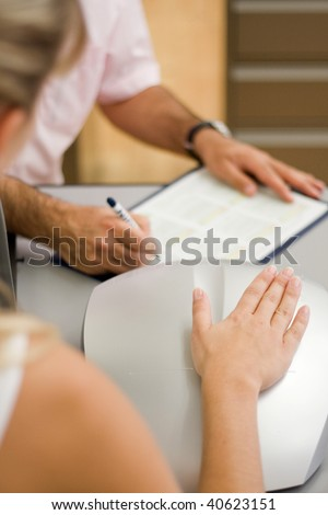 hand of a woman lies on a sensor device and a man notes some data