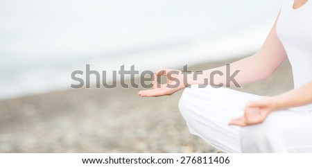 hand of a woman meditating in a yoga pose on the beach - stock photo
