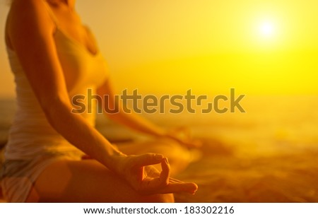 hand of a woman meditating in a yoga pose on the beach at sunset - stock photo