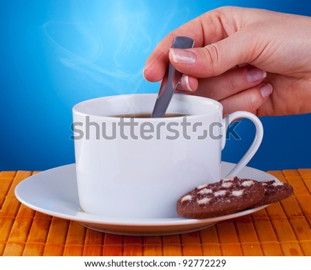 hand of a woman stiring in a fresh cup of coffee on blue background. - stock photo